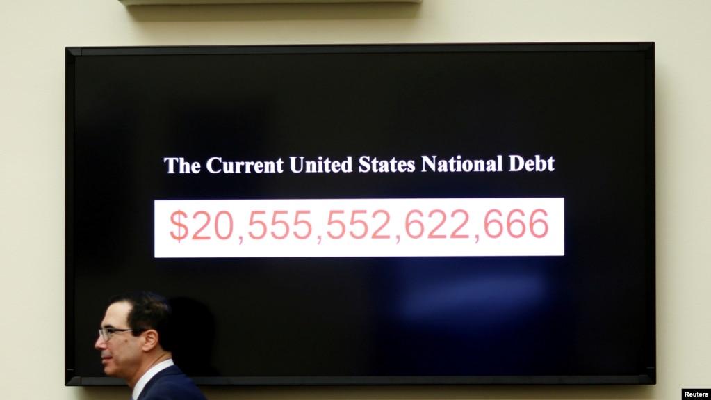 美国财政部长努钦在美国华盛顿国会山作证时走过显示美国国债的屏幕
