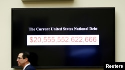 2018年2月6日美国财政部长努钦在美国华盛顿国会山作证时走过显示美国国债的屏幕。