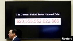 2018年2月6日美國財政部長努欽在美國華盛頓國會山作證時走過顯示美國國債的屏幕
