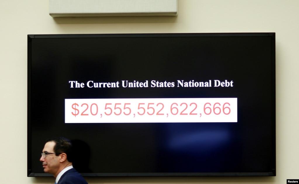 스티브 므누신 미국 재무장관이 하원 금융서비스위원회에서 '금융안정성 감독위원회의 연례 보고서'에 관해 증언한 후 연방정부 부채 규모를 나타낸 전광판 앞을 지나고 있다.