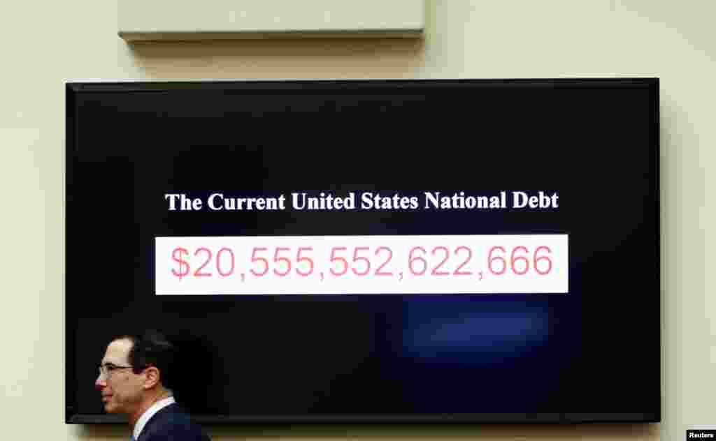 Menkeu AS Steven Mnuchin melewati papan elektronik yang memberikan informasi mengenai jumlah utang nasional Amerika saat ini di gedung Capitol, Washington DC.