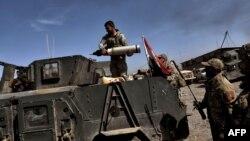 Anggota Divisi Reaksi Cepat membawa amunisi di kota Mosul sementara pasukan Irak memerangi jihadis di kota itu (26/2). (AFP/Aris Messinis)