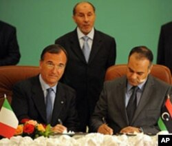 Italian Foreign Minister Franco Frattini (L) signs a memorandum of understanding with Ali al-Essawi (R), the foreign affairs chief in the rebels' National Transitional Council, in the eastern Libyan city of Benghazi, May 31, 2011