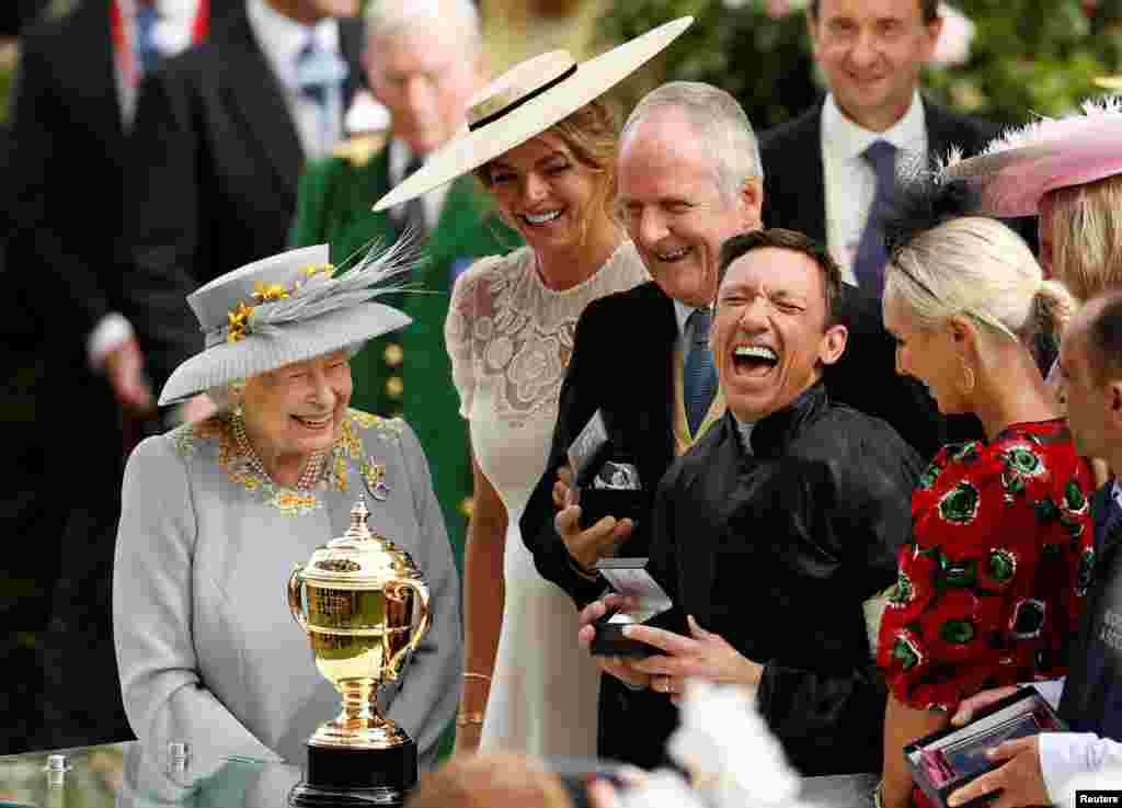 Britain's Queen Elizabeth II (L) watches as Italian jockey Frankie Dettori (R) celebrates with the trophy after he won the Gold Cup on horse Stradivarius, his fourth win of the day, on day three of the Royal Ascot horse racing meet, in Ascot, west of London.