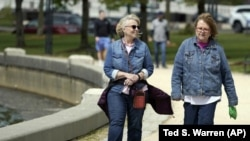 Donna Anderson, left, walks with her friend Christine White, Tuesday, April 27, 2021, in Olympia, Wash. (AP Photo/Ted S. Warren)