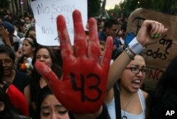FILE - People protest the disappearance of 43 students in Mexico City earlier this month.