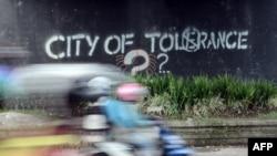 Seorang pengendara mobil melewati grafiti menyerukan toleransi di Yogyakarta, 8 Mei 2016. (Foto: AFP)
