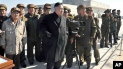 Pemimpin Korut, Kim Jong Un disertai para pejabat militer meninjau latihan artileri militer Korea Utara, Kamis (14/3).