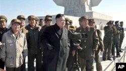 Pemimpin Korea Utara, Kom Jong Un meninjau latihan perang di sebuah lokasi pelatihan militer Korea Utara (14/3). Korea Utara menuduh Amerika dan sekutu Amerika menyerang situs-situs negaranya, termasuk KCNA, yang mengakibatkan sulitnya akses ke situs tersebut dalam waktu cukup lama pekan ini.