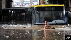 A driver wades through floodwater after his bus was stranded in a flooded tunnel in Wuhan, Hubei province. 19 Jun 2011
