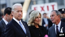 US Vice President Joe Biden (L) stands next to his wife Jill Biden and New York Mayor Mike Bloomberg (R) before dropping flowers into a reflecting pool in the middle of Ground Zero at the memorial service September 11, 2010 in New York City