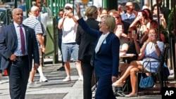 지난 11일 뉴욕에서 진행된 9·11 테러 15주기 행사에서 조기 퇴장한 힐러리 클린턴(가운데) 민주당 대통령 후보가 시내 딸의 아파트에서 휴식을 취하고 나오면서 손을 흔들고 있다. 폐렴 진단을 받은 클린턴 후보는 이후 선거운동 일정을 취소했다.