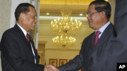 Prime Minister Hun Sen, right, shakes hands with Thai Deputy Prime Minister Trairong Suwankiri, left, in the Peace Palace in Phnom Penh.