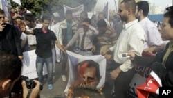 12일 이집트 카이로의 아랍연맹 본부 앞에서 알 아사드 대통령의 사진을 불태우고 있는 시리아 시위대