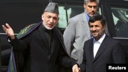 Afghan President Hamid Karzai (L) welcomes his Iranian counterpart Mahmoud Ahmadinejad upon his arrival in Kabul, March 10, 2010.