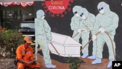 A street sweeper checks his mobile phone as he takes a break near a coronavirus-themed mural in Jakarta, Indonesia.