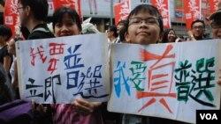 香港市民唐太太與12歲的兒子手持自製的爭取普選標語,首次參加7-1大遊行(美國之音湯惠芸)