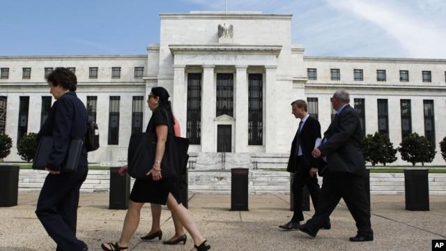 Para pekerja berjalan melewati gedung Bank Sentral Amerika di Washington DC (Foto: dok). Para pejabat tinggi Bank Sentral AS masih belum menyepakati program pembelian Obligasi untuk merangsang ekonomi Amerika, Kamis (3/1).