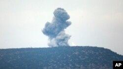 Kepulan asap dari serangan udara yang dilancarkan ke dalam wilayah Suriah, terlihat dari Provinsi Hatay, Turki, dekat perbatasan, 24 Januari 2018.