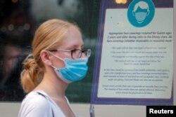 Seorang pengunjung mengenakan masker untuk melindungi dari penularanCOVID-19 menyusul rekomendasi CDC, di sebuah Disney Store.