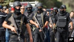 FILE - Members of the Tunisian National Guard take positions as they secure the scene of a shooting in the Oued Ellil suburb of Tunis, Oct. 23, 2014.