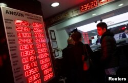 FILE - People check currency exchange rates at an exchange office in Istanbul, Dec. 16, 2014.
