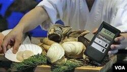 Produk makanan laut dari Jepang dipindai untuk mengetes kadar radiasinya di sebuah restoran di Hong Kong. Pemerintah mengubah posisi dengan memperketat pengawasan terhadap produk dari Jepang.