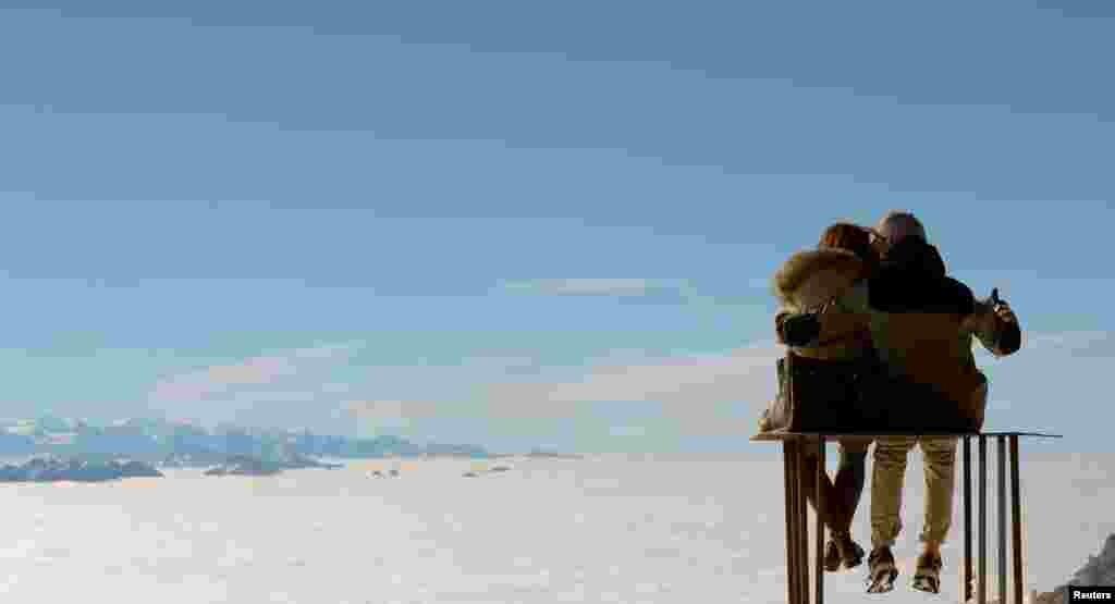 Sepasang suami istri bersantai di puncak gunung Saentis (setinggi 2.502 meter) di Schwaegalp di pegunungan Alpen timur, Swiss.