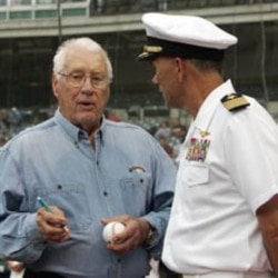 Hall of Fame pitcher Bob Feller signs a baseball for Navy Captain Frank McCulloch.