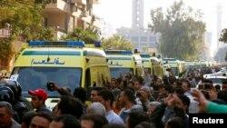 Warga mengiringi barisan ambulans yang membawa jenazah para korban pemboman Katedral Koptik di Kairo, Mesir (12/12). (Reuters/Amr Abdallah Dalsh)