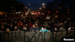 Protestors kneel as Bulgarian national anthem is played, as they block a main boulevard during demonstration against high electricity prices in Sofia, February 20, 2013.