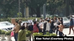Families gather outside the health department in the southern city of Guangzhou to petition against fines for couples who had more than one child before the country ended its one-child policy.