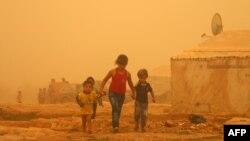 Anak-anak Suriah berjalan di tengah-tengah badai pasir yang melanda kemah penampungan pengungsi di Baalbek, Lebanon (Foto: dok).
