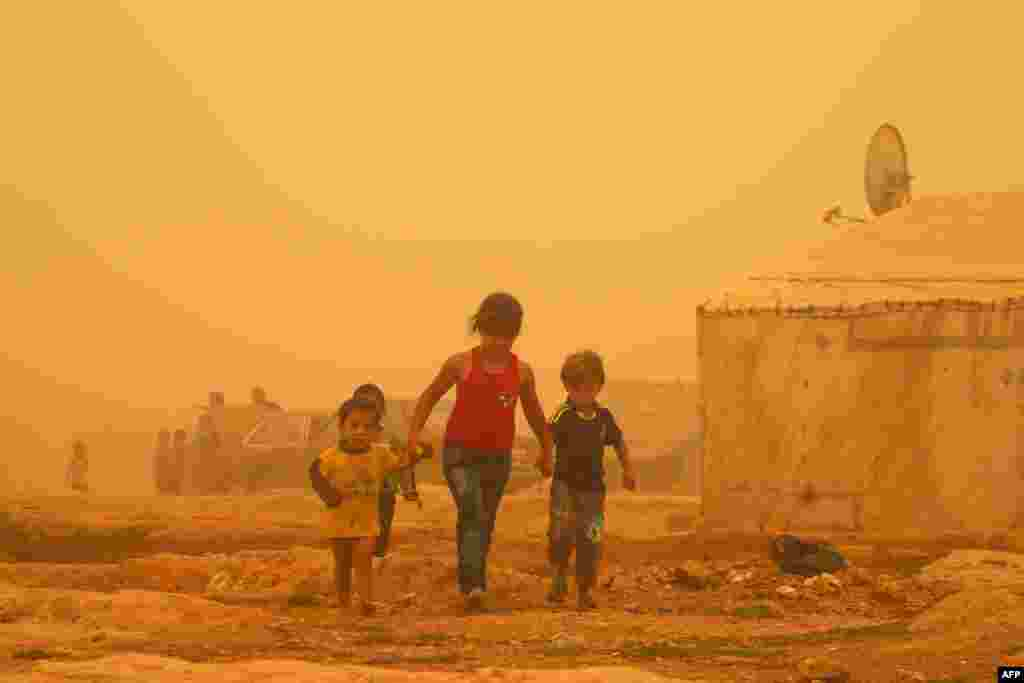 Syrian children walk amid the dust during a sandstorm at a refugee camp on the outskirts of the eastern Lebanese city of Baalbek.