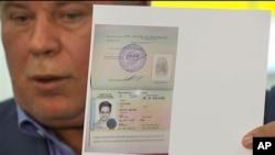 Snoudenov advokat Anatolij Kučerena pokazuje dokument o privremenom azilu kojim se Edvardu Snoudenu omogućuje da udje u Rusiju.