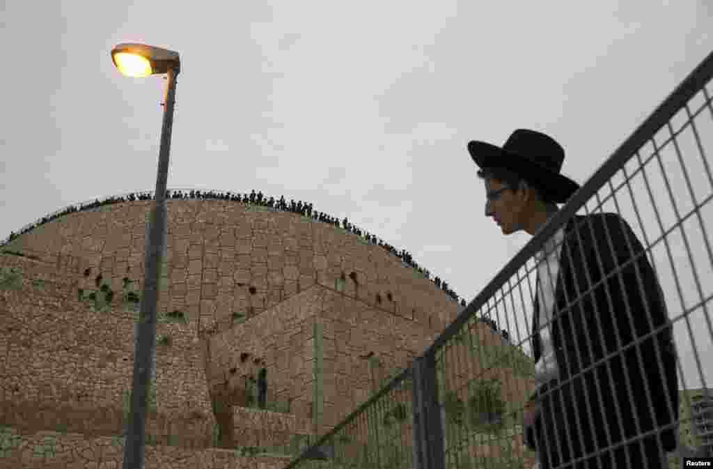 Một người đưa tang đứng xem buổi lễ an táng 7 em nhỏ trong gia đình Sassoon ở Jerusalem. Bảy em nhỏ trong gia đình Do Thái Chính thống giáo này tử vong khi hỏa hoạn bùng lên trong căn nhà của họ ở quận Brooklyn trong một trong những vụ hỏa hoạn làm chết người nhiều nhất ở thành phố New York những năm qua, nhà chức trách cho biết.