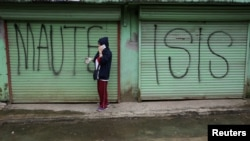 "FILE - A man is seen using a mobile phone while passing a shuttered store front with ""MAUTE-ISIS"" graffiti, in Marawi city, southern Philippines, Oct. 20, 2017. Maute, an Islamic State affiliate, was among groups the U.S. added to its terror list Tuesday."
