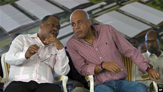 Haiti's President Michel Martelly (R) speaks with Haiti's Prime Minister Garry Conille at a ceremony on the outskirts of Cap Haitien, Haiti, November 28, 2011.