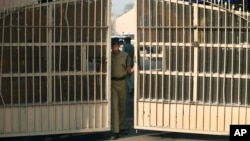 FILE - An Indian police officer is seen closing the gates of a prison in New Delhi, India.