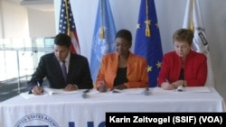 "From left to right: USAID Administrator Rajiv Shah, UN Emergency Relief Coordinator Valerie Amos and EU Humanitarian Commissioner Kristalina Georgieva sign a ""call to action"" aimed at averting famine in South Sudan, in Washington on Sat. April 12, 2014."