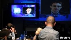 Para wartawan mendengarkan pertanyaan Edward Snowden, di sebuah Media Center di Moskow, saat berlangsungnya acara siaran langsung bersama Presiden Rusia Vladimir Putin, 17 April 2014 (Foto: dok).