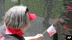 Beth Cullom finds the name of a family friend, John Barovetto, who was killed in Vietnam, 31 May 2010