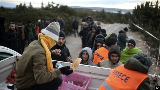 Migrants queue to get free food as they wait to travel to Greek islands by dinghies, near Cesme, Izmir, Turkey, late Thursday  Dec. 31, 2015.