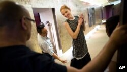 Fashion designer Carmen Marc Valvo, left, watches, as his model Taylor Foster and creative director Il Park work on a dress in a hallway that doubles as a runway at Valvo's New York studio, Aug. 30, 2013.
