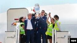 L'entraîneur du Portugal Fernando Santos, à gauche, et le capitaine Cristiano Ronaldo, à droite, sortent de l'avion brandissant le trophée de l'Euro 2016, à l'aéroport Humberto Delgado à Lisbonne, Portugal, 11 juillet 2016. epa / MARIO CRUZ