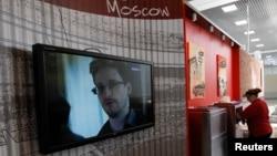 Sebuah layar televisi menyiarkan gambar mantan kontraktor badan intelijen AS Edward Snowden di sebuah kafe di bandar udara Moskow (26/6).