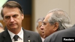Federal deputy Jair Bolsonaro, left, a candidate for the Presidency of the Republic for the Social Liberal Party listens to economist Paulo Guedes before a lunch with businessmen at the Federation of Industries of Rio de Janeiro headquarters in Rio de Janeiro, Aug. 6, 2018.