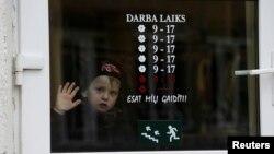 Seorang anak laki-laki melongok dari jendela toko di Valka, Latvia (25/10).