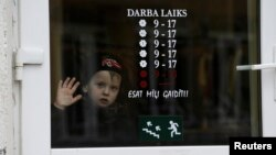 FILE - A boy looks through a shop window in Valka, Latvia, Oct. 25, 2013.