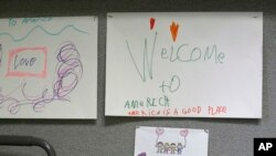 "Children's drawings that read ""Welcome to America, America is a good place,"" are displayed, April 24, 2017, at a Jewish Family Service Refugee and Immigrant Service Center in Kent, Washington, during a visit by Washington Gov. Jay Inslee."